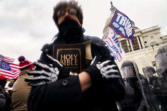 A man holds a Bible in his hand this Wednesday, January 6, 2021 as President Donald Trump's supporters gather outside the Capitol in Washington.