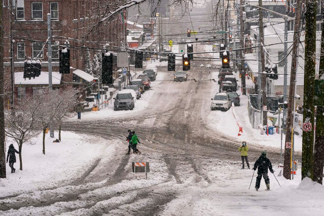 A skier walks down a hill in Seattle, Washington on February 13, 2021.