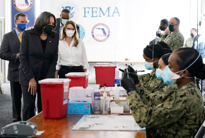FEMA Regional Administrator Gracie Szczech, center, takes Vice President Kamala Harris on a tour of the Jacksonville Community Vaccination Center in Florida, where Navy members prepare Pfizer vaccines on March 22nd.