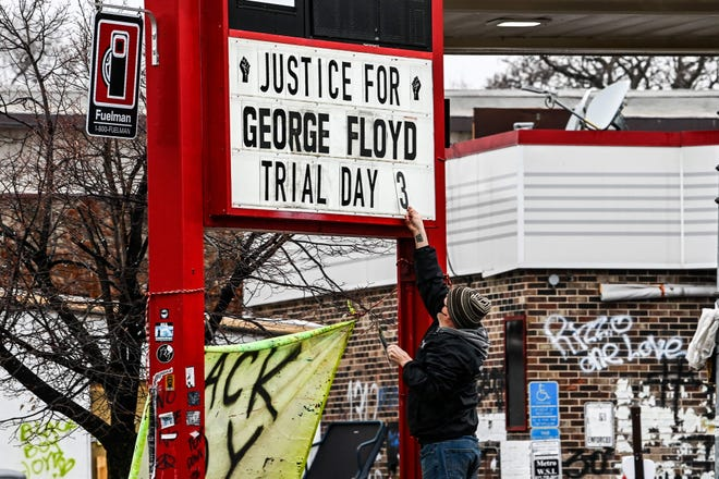 A man changes the number of a placard on a makeshift memorial dedicated to George Floyd before the third day of jury selection begins in the trial of former Minneapolis police officer Derek Chauvin, who is accused of being Floyd on March 10, 2021 in Minneapolis, Minnesota, to have killed.