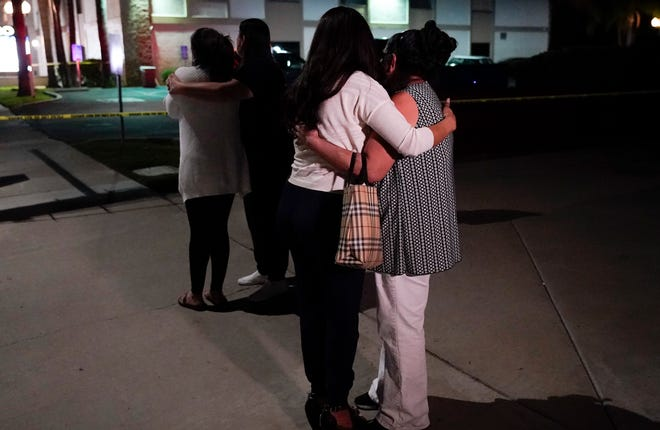 People comfort one another near a company that suffered a shootout in Orange, California.  According to authorities, 4 people, including a child, died in the March 31 shooting.