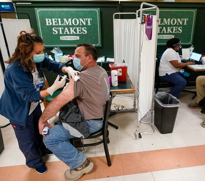 A nurse (left) inoculates a metal worker with a dose of the COVID-19 Pfizer vaccine at a coronavirus vaccination site in Belmont Park in Elmont, New York, Wednesday.