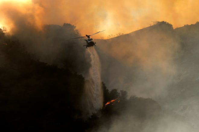A fire helicopter drops water on a bushfire in the Pacific Palisades area of Los Angeles on May 15, 2021.