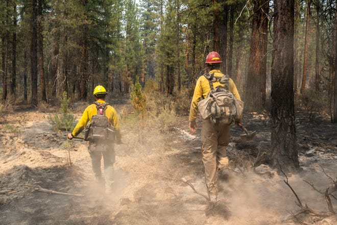 Firemen Garret Suza (right) and Cameron Taylor of the Chiloquin Forest Service are searching for hotspots near the Sprague River, Ore, on the northeast side of the Bootleg Fire on Wednesday, July 14, 2021.