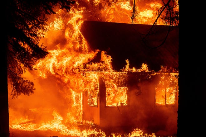Flames devour a home as the Dixie Fire ripped through the Indian Falls community in Plumas County, California on Saturday, July 24, 2021.