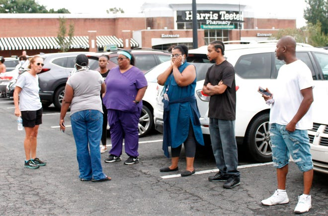 Concerned parents are standing in the parking lot of a mall in Winston-Salem, NC on Wednesday, September 1, 2021.  A student was killed in a shooting at a North Carolina high school Wednesday and authorities were looking for the suspect, officials named.