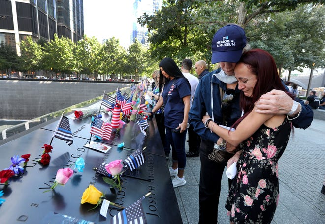 Mercedes Arias, formerly from Yonkers, NY, is comforted by a 9/11 Museum employee as she cries next to the name of her father Joseph Amatuccio at the 9/11 Memorial on September 11, 2021, on the 20th anniversary of the 9/11 attacks.  Her father, who worked in the World Trade Center, died in the attacks.