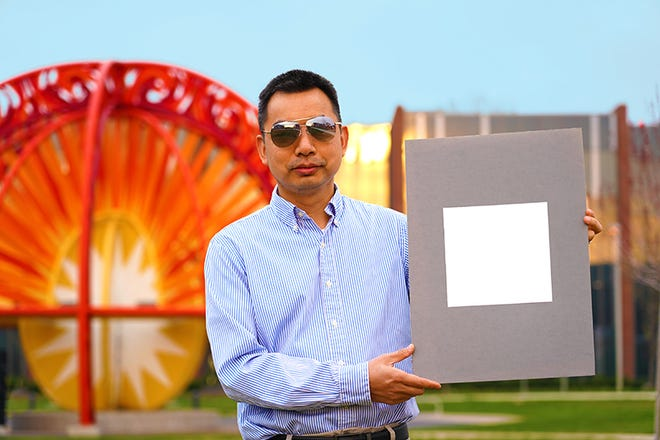 Xiulin Ruan, professor of mechanical engineering at Purdue University, holds up his laboratory sample of the whitest color ever.